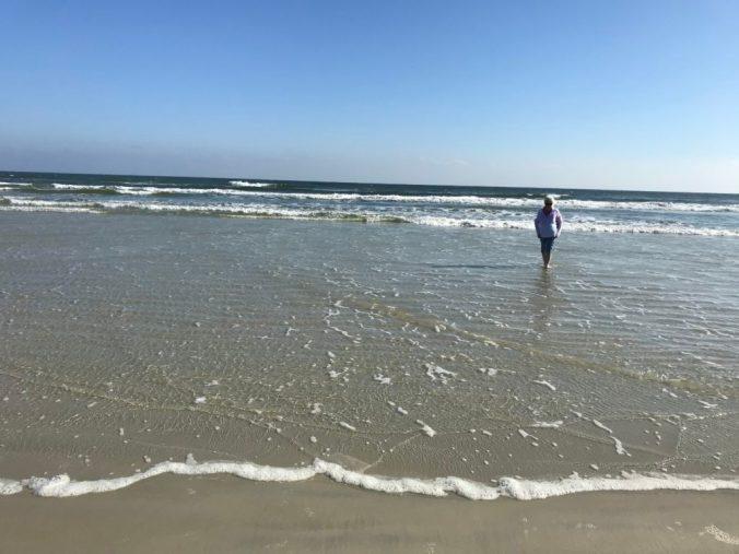 woman wades in ocean under a blue sky