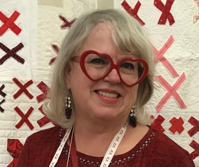 woman with pewter colored hair and red heart-shaped glasses stands in front of a white quilt covered in pairs of red X's