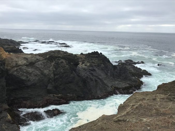 massive, mountainous rocks surrounded by light blue ocean under gray skies