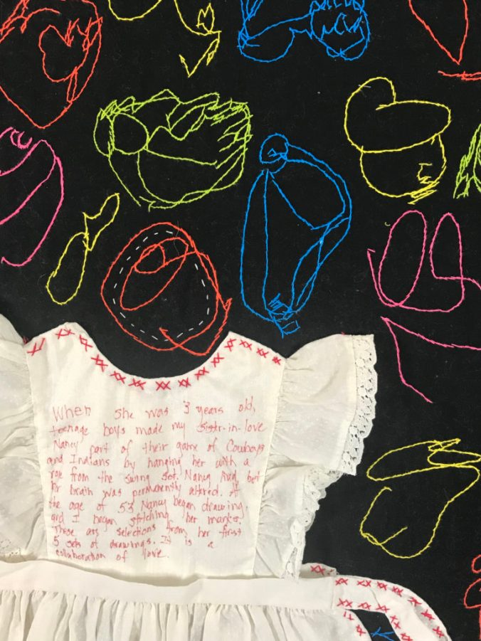 closeup of the white dress sewn onto a black quilt covered with colorful stitched scribbles
