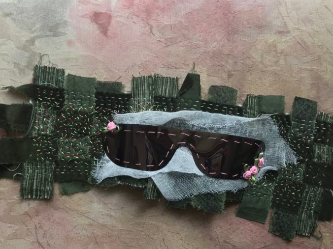shades used after eye dilation sewn to strips of green fabric woven together adorned with multi-colored stitches