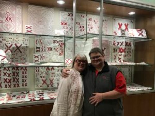 two women stand in front of a glass display case filled with white quilts covered with pairs of red X's