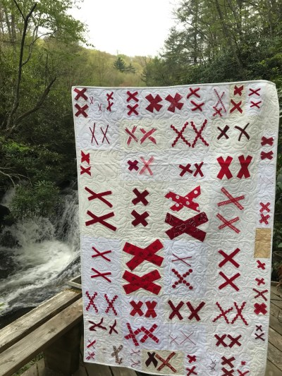 a white quilt covered with pairs of red X's is displayed beside a waterfall