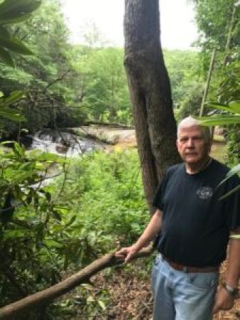 man stands beside a railing overlooking a waterfall