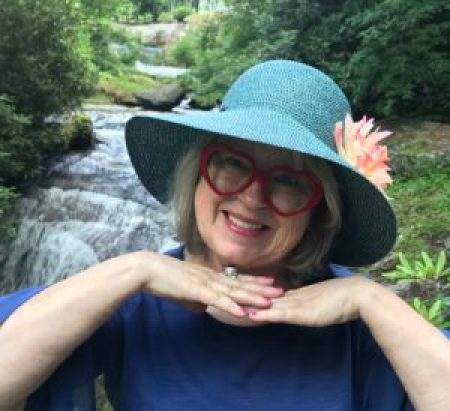 smiling woman wearing red heart-shaped glasses wearing a blue hat with a big pink flower stands in front of a waterfall
