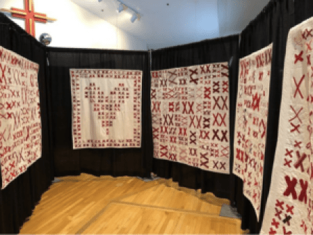 5 white quilts covered in pairs of red X's hanging on a black background