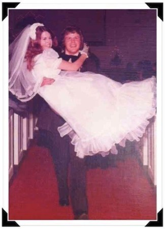 man carries woman in wedding dress out of church