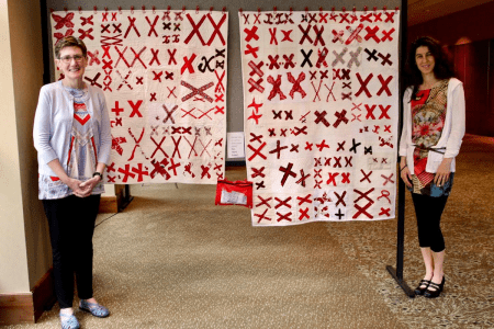 two white quilts covered in pairs of red X's hang between two women