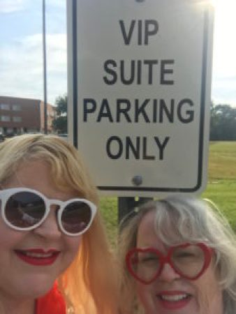 two women stand in front of a sign that says