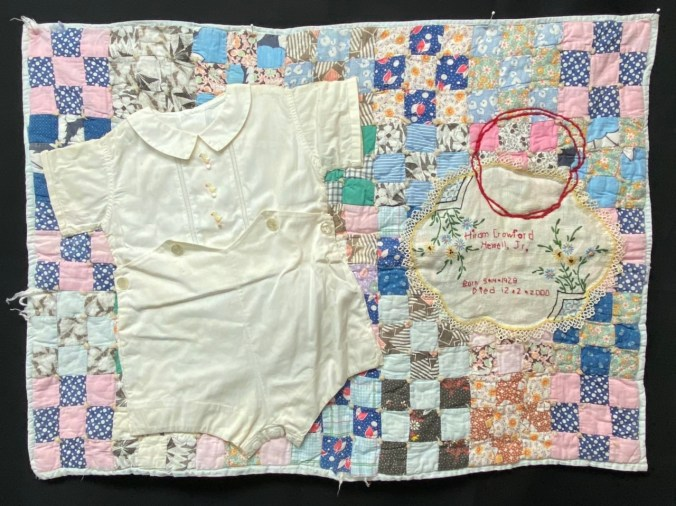 Vintage boy's shorts and shirt, vintage embroidered doilie, two red embroidered circles, all appliqués to the top of a small vintage quilt