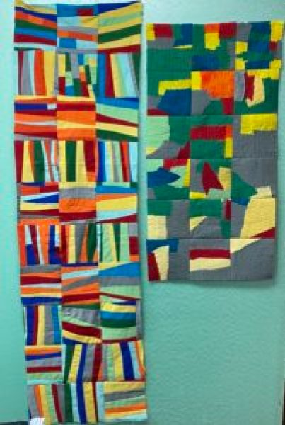 Red, yellow, blue, green, gray, and orange pieces of fabric sewn together into blocks