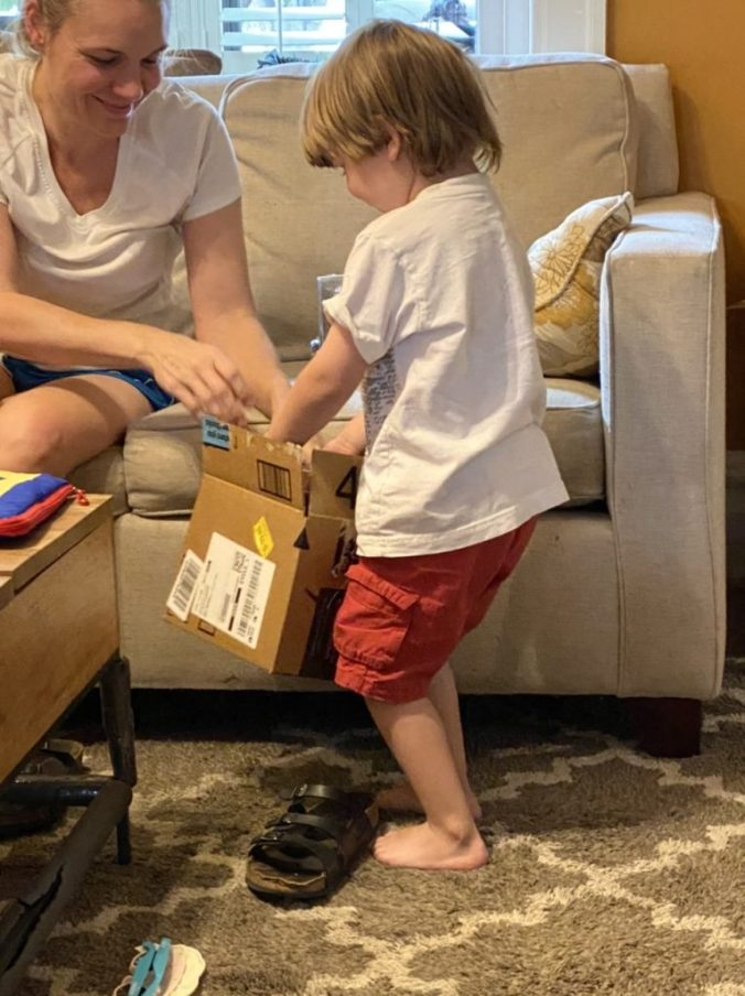 a young boy opens a box with the help of a woman