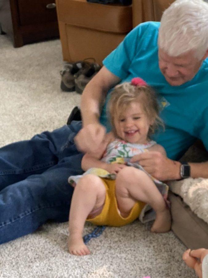 a man tickles a little girl