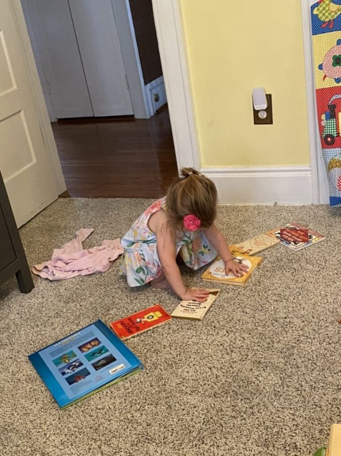 a girl plays with books ont he floor and makes stepping stones