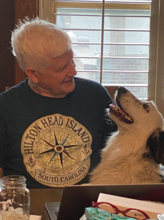a man and a dog smiling at each other