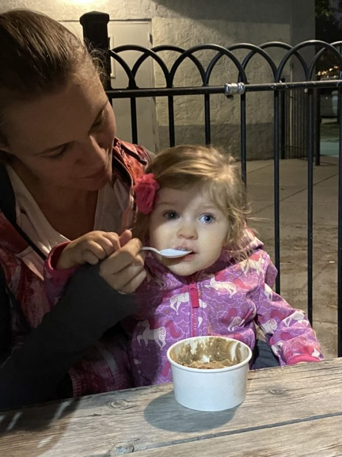 a woman feeds a little girl a spoonful of ice cream