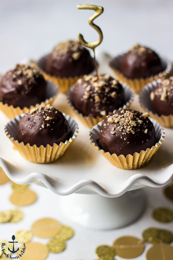 Pecan Pie Truffles in gold foil cups on a white cake pedestal  with a number 3 pick in center truffle.