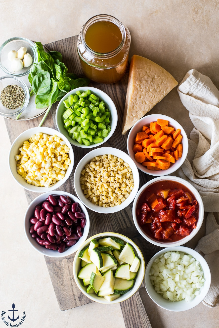 Overhead photo of ingredients for summer minestrone soup in individual bowls