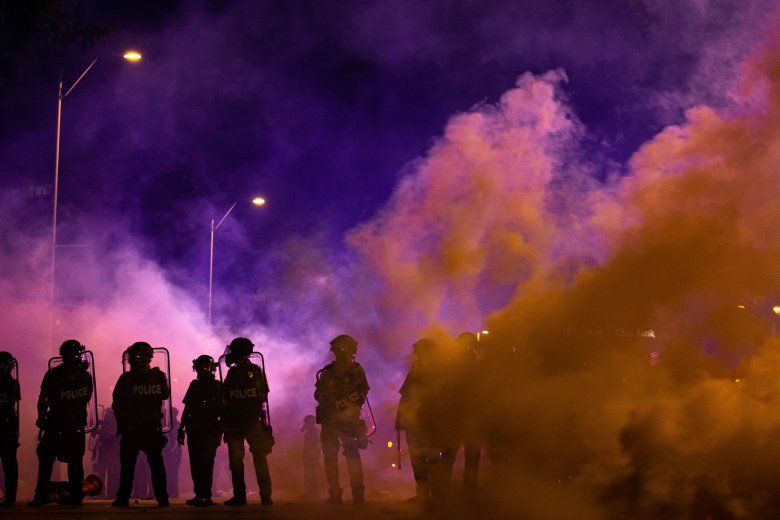 Kansas City officers stand unmoved amid tear gas during protests against police brutality on May 30, 2020. Zachary Linhares/The Beacon