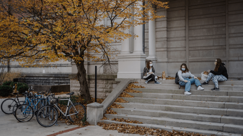 From left, University of Missouri juniors Devon Terry, Sydney Greenfield and MaryRose Ornosky eat food and hang out at Jesse Hall on Tuesday Nov. 10, 2020, on MU's campus. When the sun set, the three students departed separately. Jacob Moscovitch/The Beacon