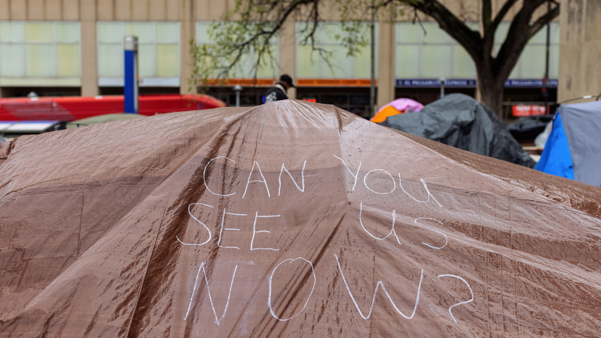 "A hand drawn sign reads, ""Can you see us now?"" on a tarp covering tents at the Kansas City Homeless Union's City Hall occupation on April 7."