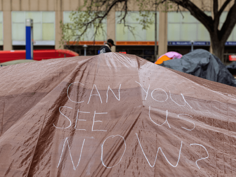 """A hand drawn sign reads, """"Can you see us now?"""" on a tarp covering tents at the Kansas City Homeless Union's City Hall occupation on April 7."""