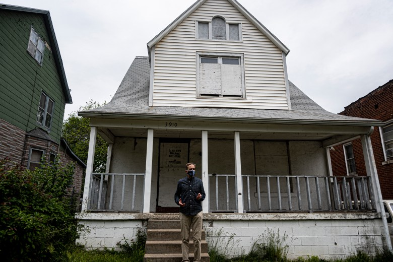 Gregg Lombardi stands in front of a home classified as a dangerous building in the Lykins Neighborhood of Kansas City, Missouri.