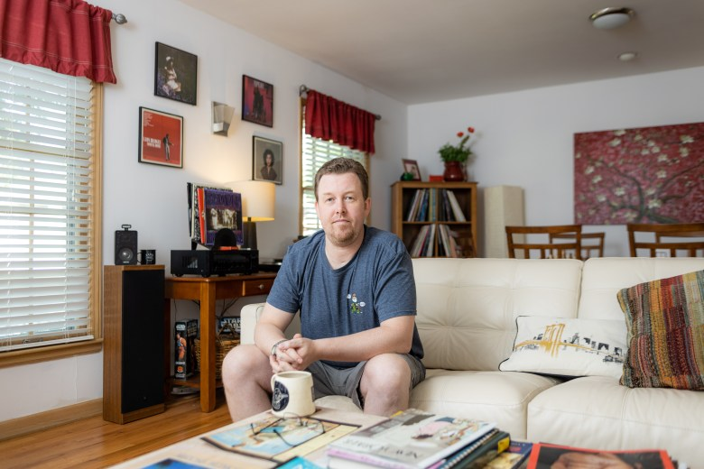 Brandon Smith sitting in his living room in the house he bought in north Kansas City. He experienced the ups and downs of Kansas City's housing market.