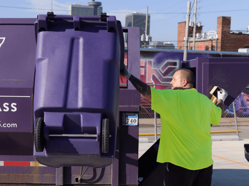 A ripple glass worker empties a purple bin with glass recyclables into a truck.