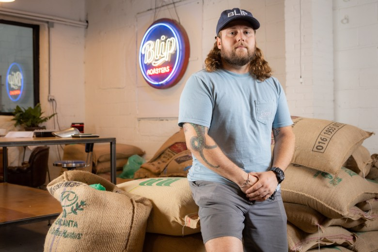 Ian Davis stands in front of a bag of coffee beans at Blip Coffee Roasters in the West Bottoms.