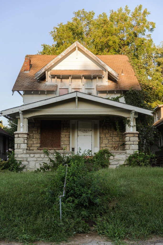 """The Land Bank-owned dangerous building at 4024 Bellefontaine in Kansas City, MO. Vegetation has grown over nearly the entire north side of the house. A sign painted on the door reads, """" Secured by the city of KCMO. No trespassing."""""""