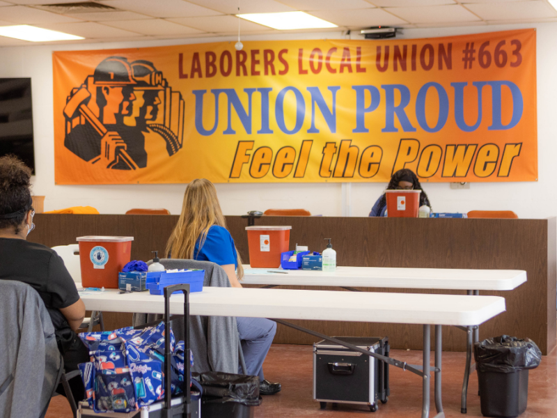 """A banner that reads """"Laborers Local Union #663, Union Proud, Feel the Power"""" behind two tables set up for vaccination."""