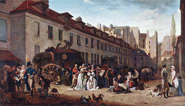 Street scene in front of a coach house with people talking while the coach is loaded in the background