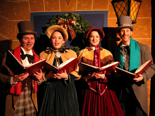 Group of carolers in Victorian costume holding music books and singing