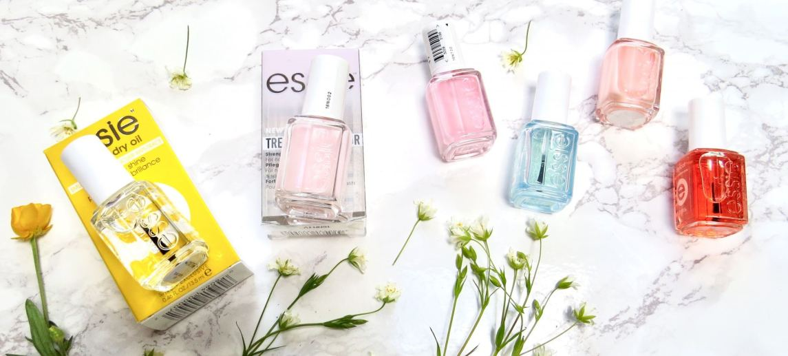 Essie treatments scattered on a marble background