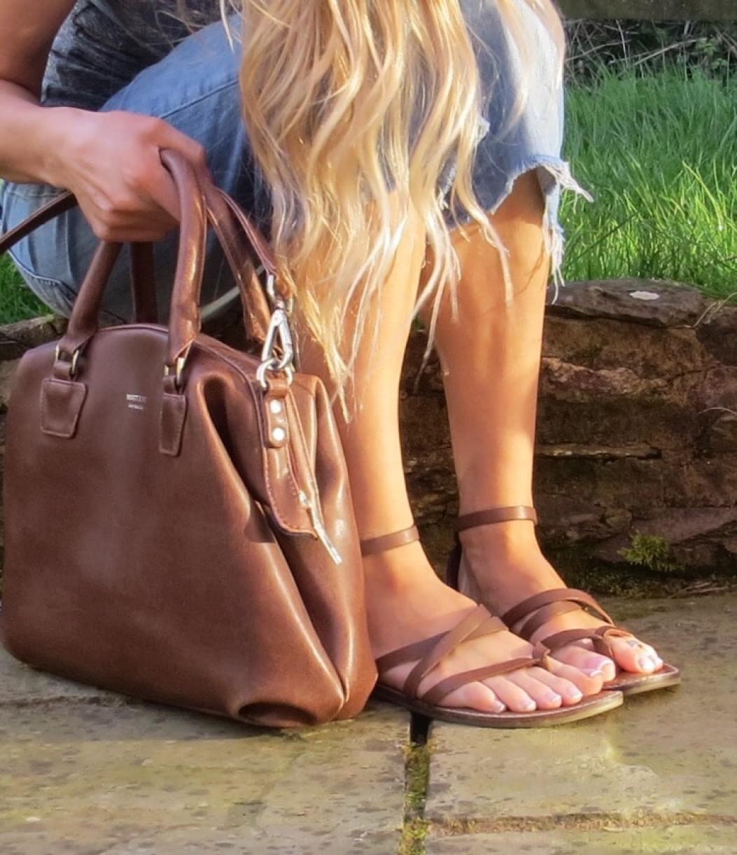 Samantha wearing brown sandals and holding a brown matt and nat handbag