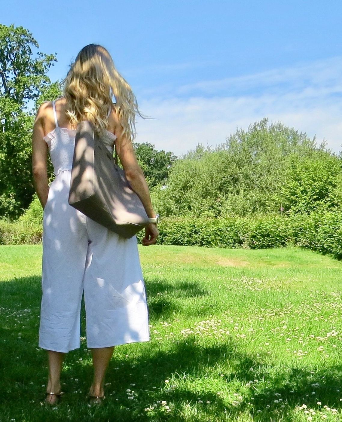 Image shows samantha from behind wearing Asos white jumpsuit. The white edit.