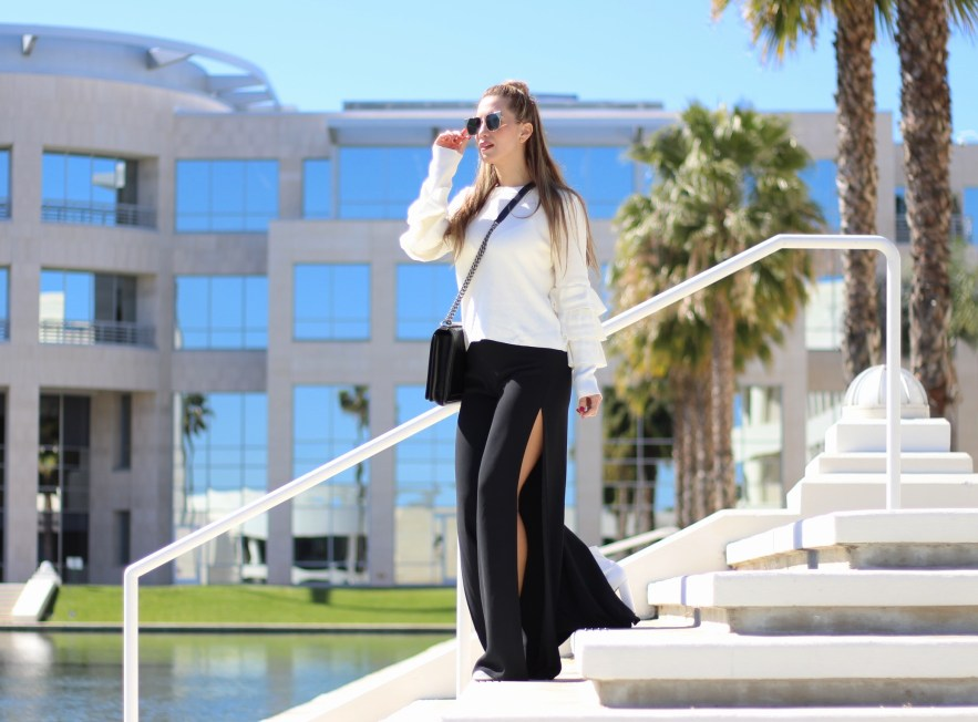 woman wearing a white sweater paired with black trousers in a unique design