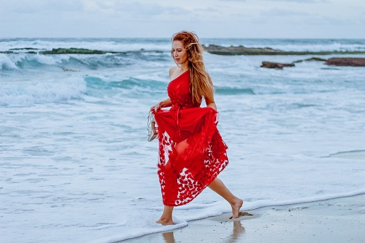 woman wearing a red gown. She is standing on a rock admiring the sea.