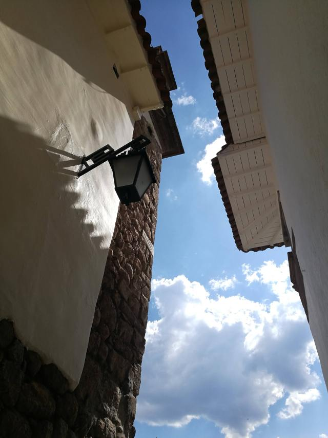 Through a gap in the roofs of some old buildings in Cusco, the sky is bright blue. A few fluffy clouds float by.