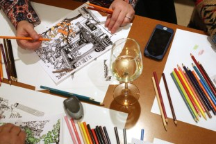 """Visitors color in pages during an adult coloring night at the Market 65 restaurant in Columbus, Ohio on November 20, 2014. The evening was created to promote """"The Columbus Ohio Coloring and Activty Book"""" created by Katie Barron. The book features various Columbus scenes that encourage the artist to color in their own ideas about what shade the subject should be. The adult coloring nights allow guests to drink wine and talk while they color the pages. (Columbus Dispatch photo by Brooke LaValley)"""