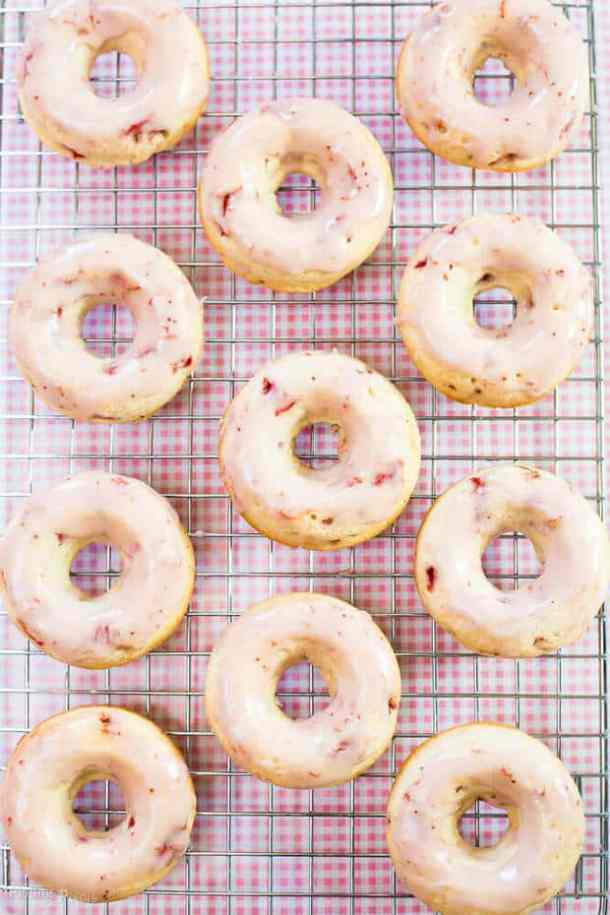 Chocolate Strawberry Glazed Doughnuts -- Baked donuts, not fried, with fresh strawberries and lemon zest. Topped with homemade strawberry glaze! | Featured on www.thebestblogrecipes.com