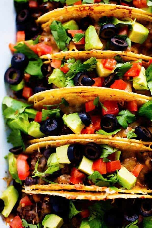 Beefy Baked Tacos are ready for the dinner table in under 30 minutes! They are layered with refried beans, a black bean taco seasoned ground beef and topped with melty cheese. Load them up with all of your favorite toppings and your family will devour them