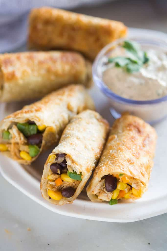 Crispy Southwest Egg Rolls (that you can bake or fry!) served with a creamy cilantro dipping sauce. These could be my favorite party appetizer of all time, (and they're freezer friendly)!