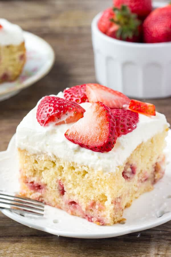 Homemade strawberry cake is super moist, with a delicious vanilla flavor and bursting with fresh berries. Then it's covered with a sweetened whipped cream topping and even more strawberries.