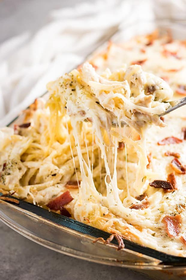 The best ever chicken spaghetti that is easy to make! This mouthwatering chicken spaghetti casserole is rich and hearty, full of cream cheese, bacon, sour cream, parmesan, mozzarella, tender chicken, and spaghetti noodles baked to perfection!