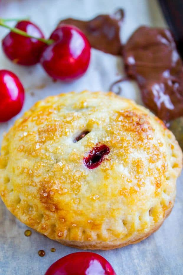 Flaky andbuttery mini pies filled with fresh summer cherries and melty chocolate! The chocolate has a touch of almond in it. These are so perfectly cuteit's hard not to throw down like 8 at a time.