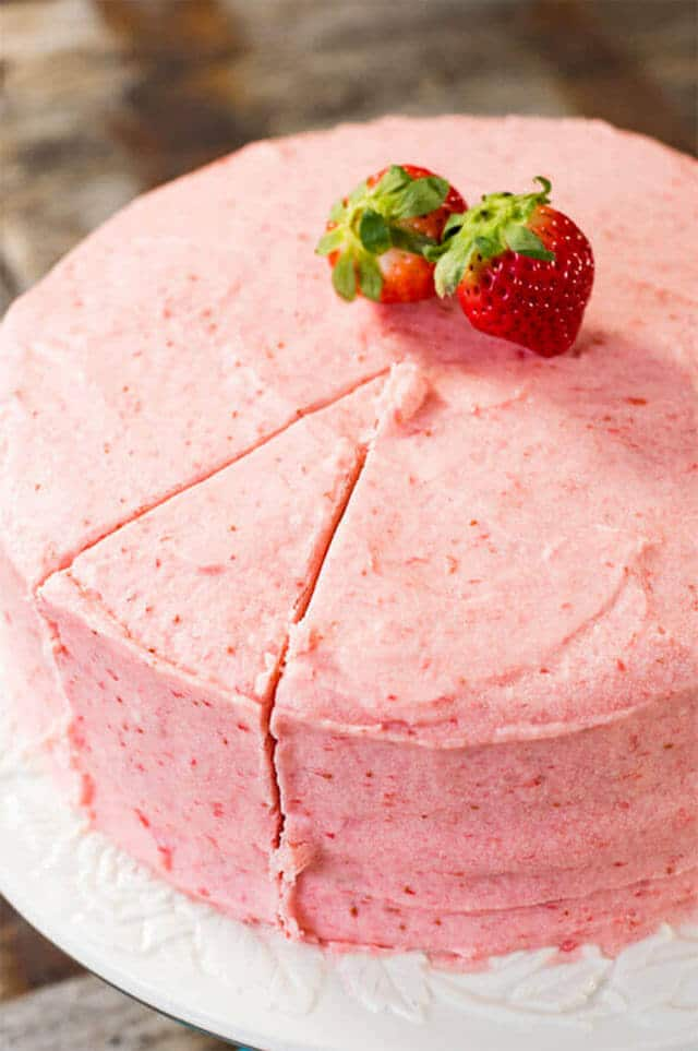 A close up of a strawberry cake with one slice cut