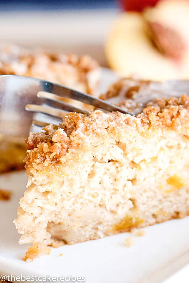 peach coffee cake with streusel on a plate with a fork
