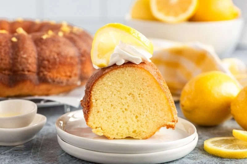a piece of lemon pound cake on a plate with lemon and whipped cream